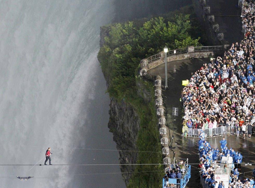 Nik Wallenda nears the Canadian side of Niagara Falls by tightrope, attracting 100,000 spectators