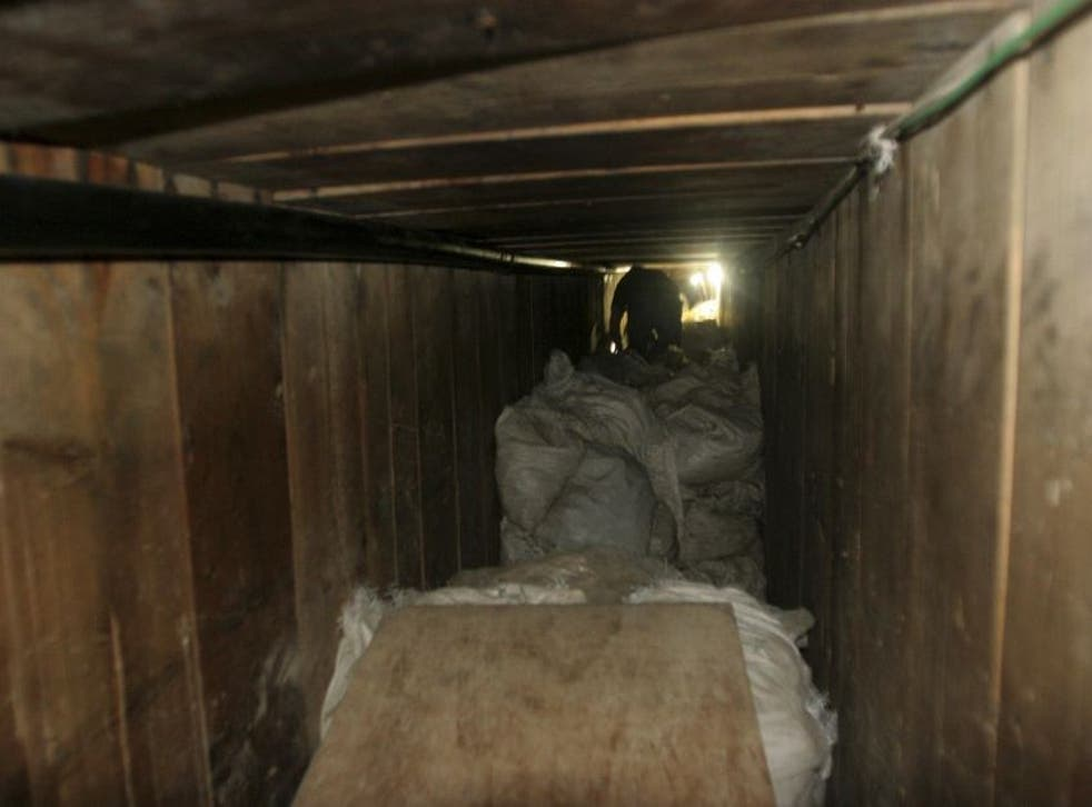 A reporter crawls through one of the tunnels discovered under a sink in a warehouse in Tijuana