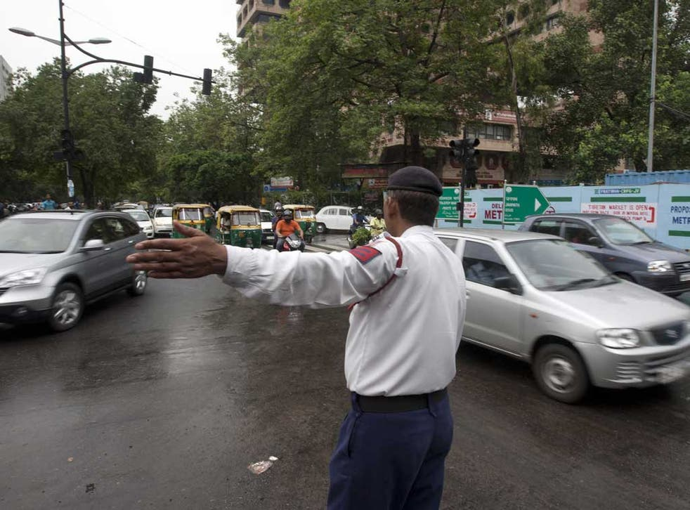 An Indian traffic police officer directs traffic at an intersection during a power outtage in New Delhi