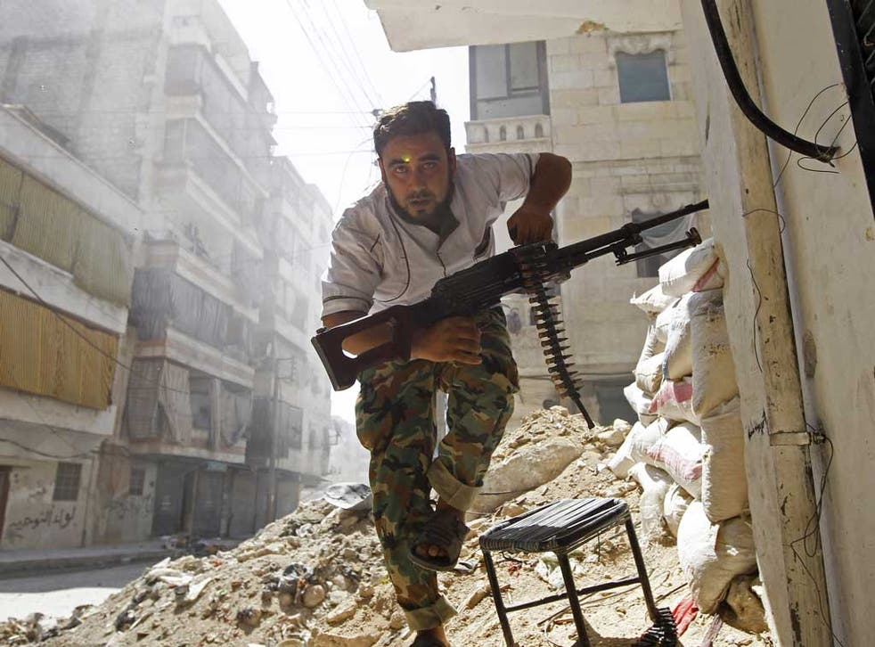 A Free Syrian Army fighter takes cover during clashes in Aleppo