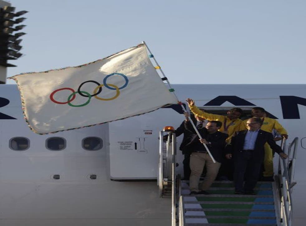 Rio mayor Eduardo Paes waved the five-ringed flag as he and other officials disembarked from the flight that brought them back from London