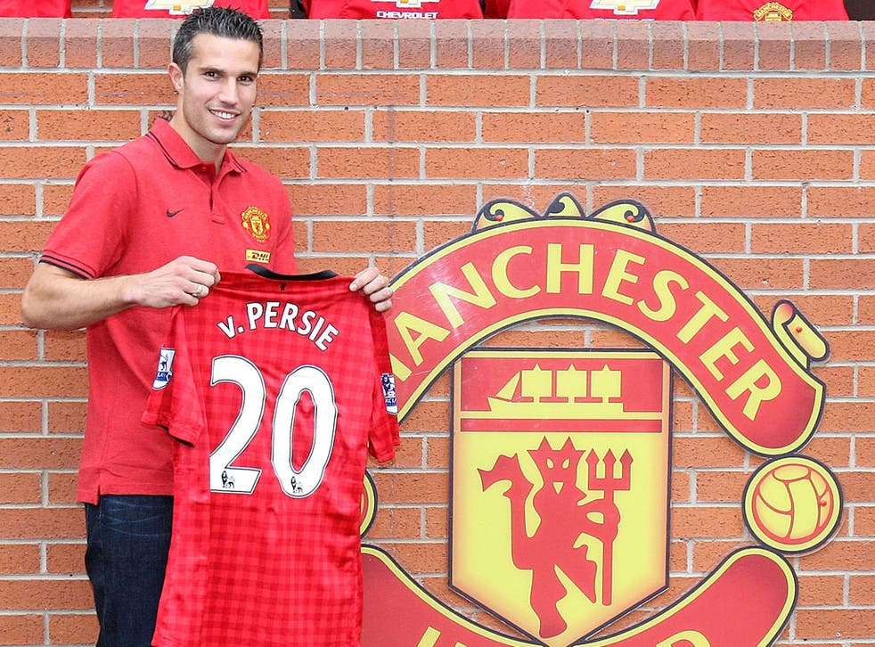 A delighted Robin van Persie poses with his new Manchester United shirt