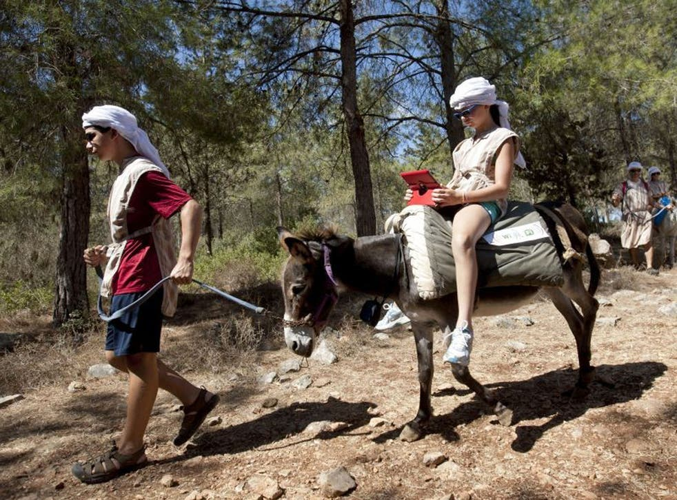 American tourist Ella uses an iPad while riding a Wi-Fi-outfitted donkey