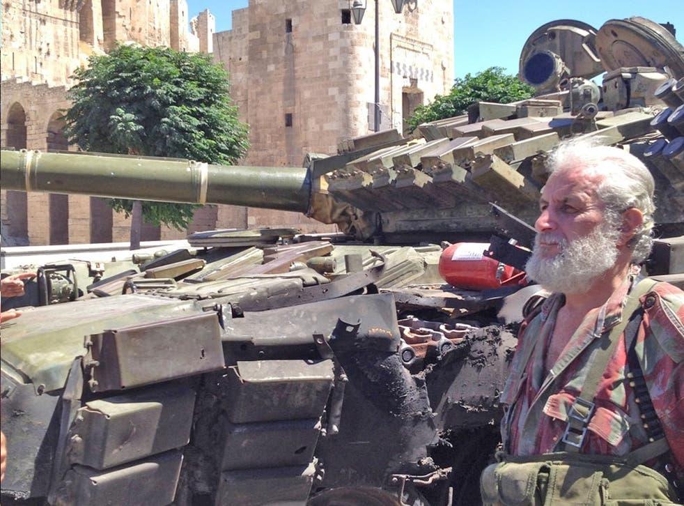 Private Abul Fidar of the Syrian army stands beside a damaged T-72 tank below the Aleppo Citadel
