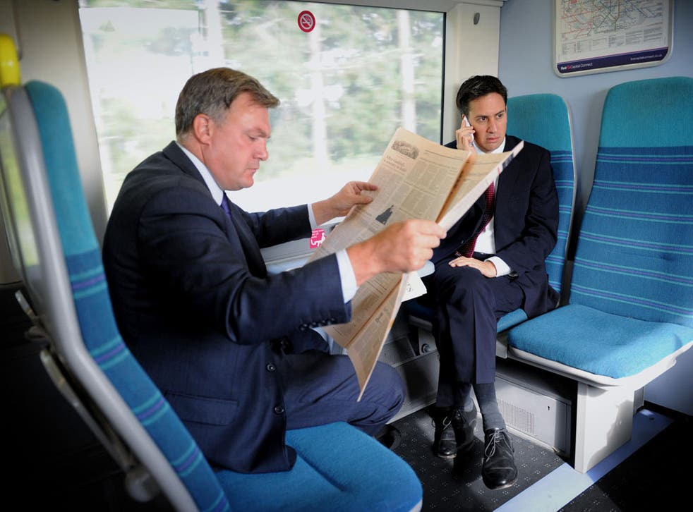Quiet area: Ed Balls and Ed Miliband travel together - but separately