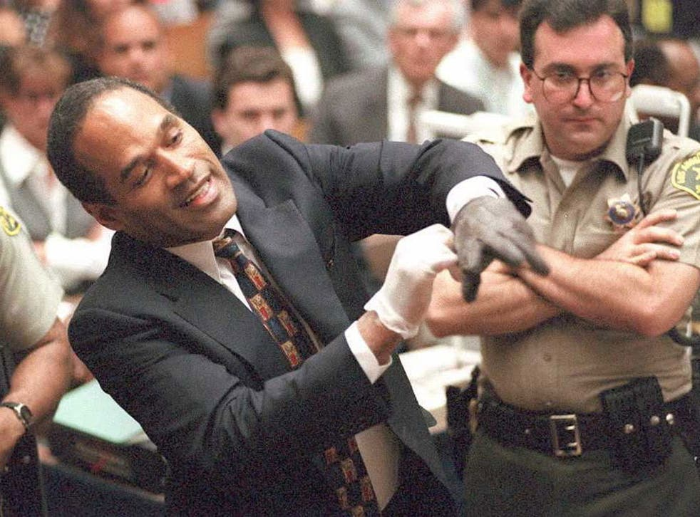 Evidence: O J Simpson, above, trying the infamous glove at his trial