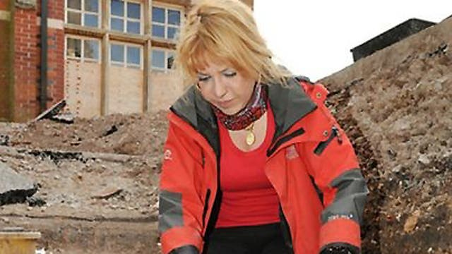 A University of Leicester photograph of Karen Ladniuk, from the Richard III society, cleaning a path made from re-used medieval tiles during the excavation of the car park behind council offices in Leicester