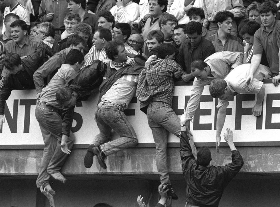 Supporters are pulled to safety in the upper tier of the Leppings Lane stand