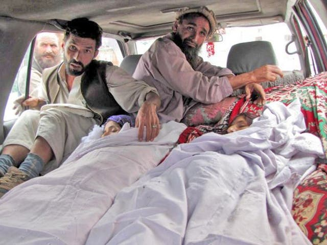 Relatives accompany the bodies of Afghan women reportedly killed in a Nato airstrike in Laghman Province as they collected wood