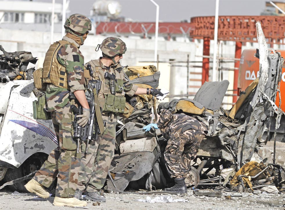 Isaf soldiers survey the wreckage of a minibus destroyed by a suicide bomb in Kabul yesterday. The attack was in response to the anti-Islam film 'The Innocence of Muslims'