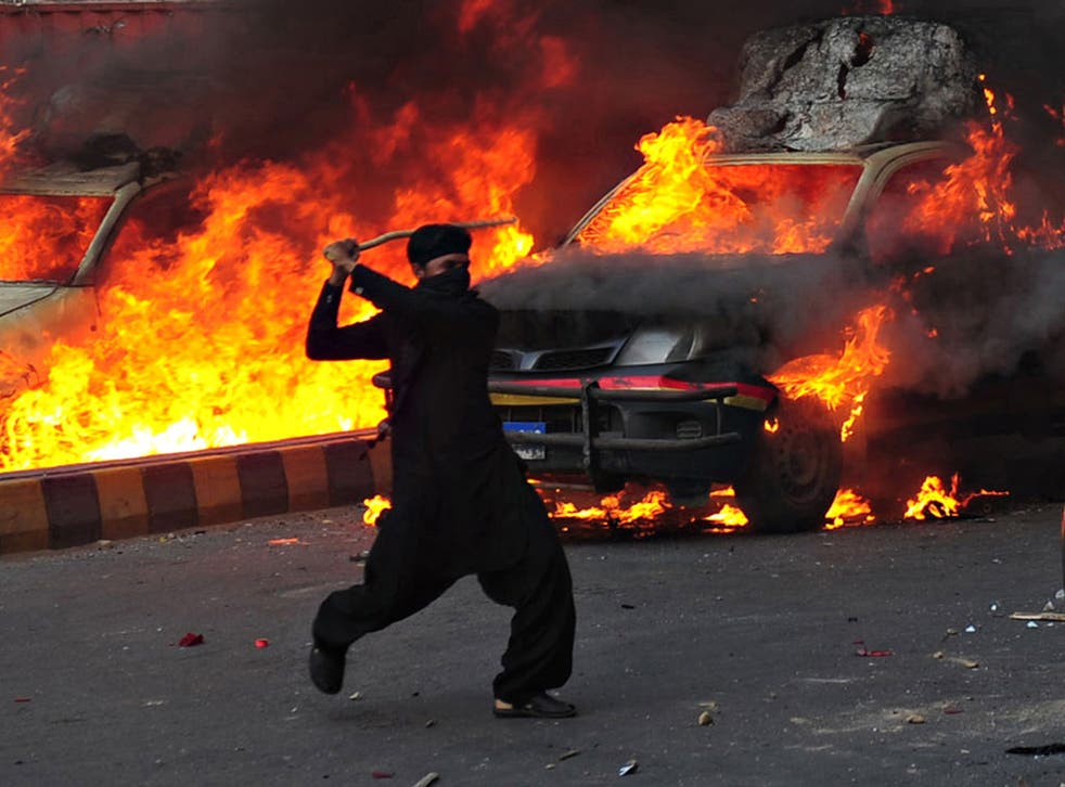 A Pakistani Muslim demonstrator brandishes a stick near burning police vehicles during a protest against an anti-Islam film in Karachi