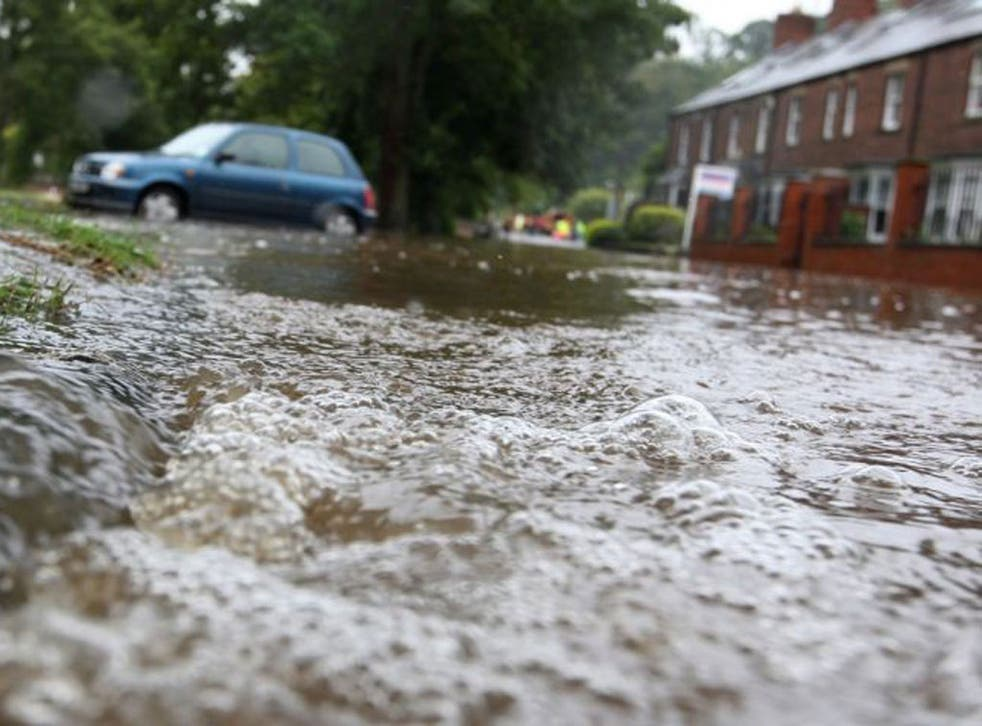 Flood waters pours into a residential street after the River Wansbeck broke its banks in Morpeth