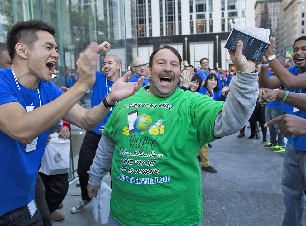 A happy customer is cheered on as he celebrates with his newly purchased iPhone 5 in hand outside the Fifth Avenue Apple store, in New York