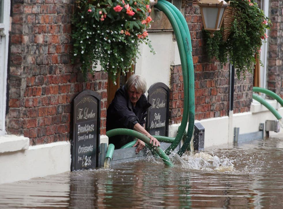 A pub landlord battles with River Ouse floodwater in York this week