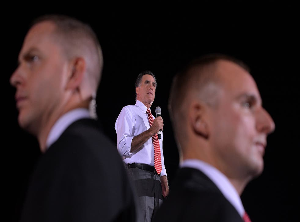 US Republican presidential candidate Mitt Romney speaks as secret service members keep guard during a campaign rally in Fishersville, Virginia