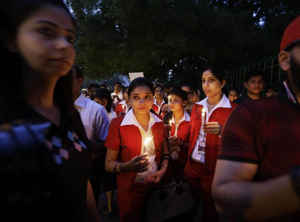 Employees of Kingfisher Airlines, owned by Vijay Mallya, inset,  take part in a candlelight vigil after the wife of a colleague killed herself