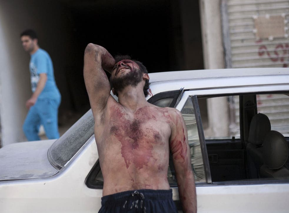 Grief and pain: Outside an Aleppo hospital after Syrian planes attacked a school last week