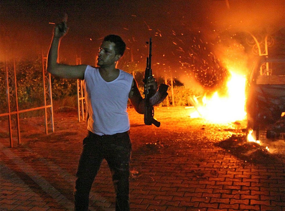 An armed man waves his rifle as buildings and cars are engulfed in flames after being set on fire inside the US consulate compound in Benghazi last month