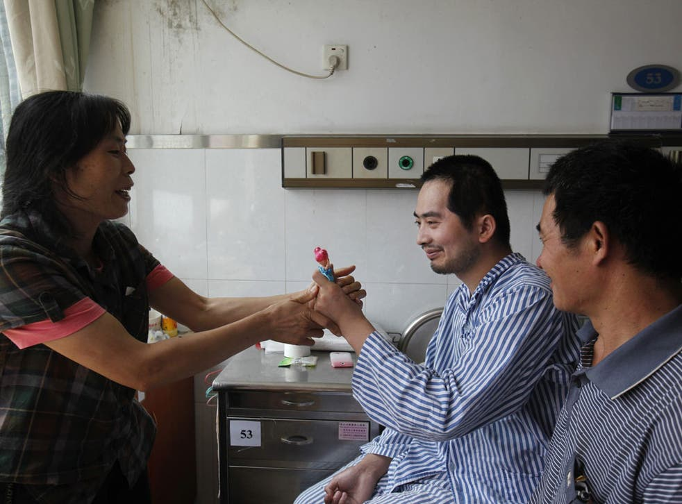 Zhang Tingzhen, who is unable to speak or walk properly, with his parents in Shenzhen hospital