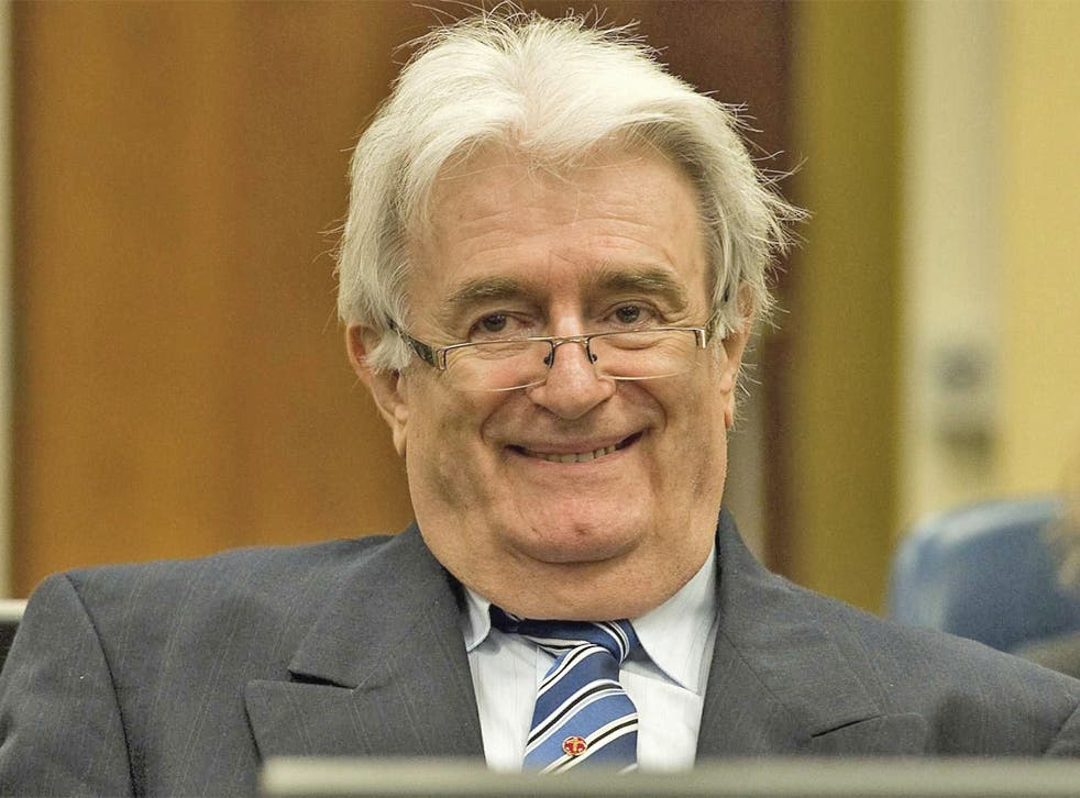 Radovan Karadzic sits in the courtroom on the first day of his defense against war crime charges