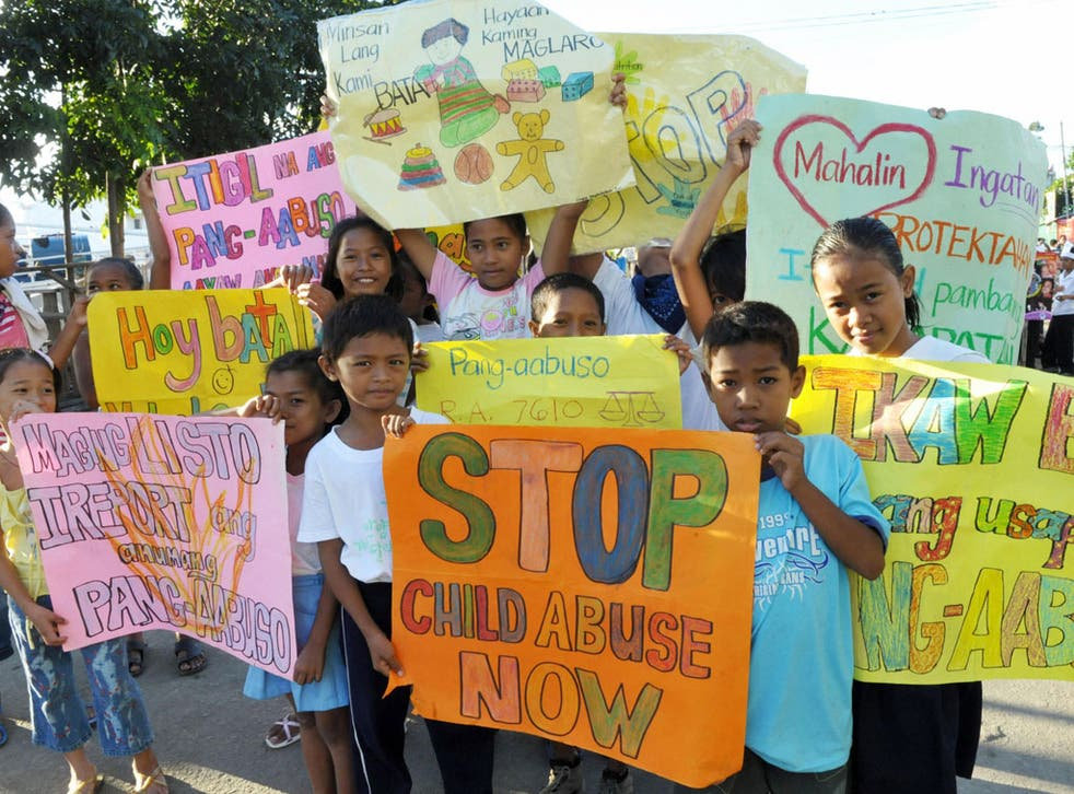 Children from the depressed area of Baseco in Manila on October 17, 2008 carry signs calling for the end of child abuse, in a parade marking United Nations Childrens Month.