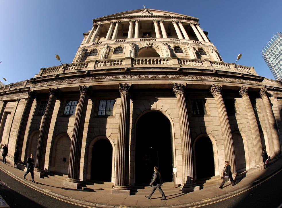 Businessmen walk past the Bank of England in the financial district in London, England.