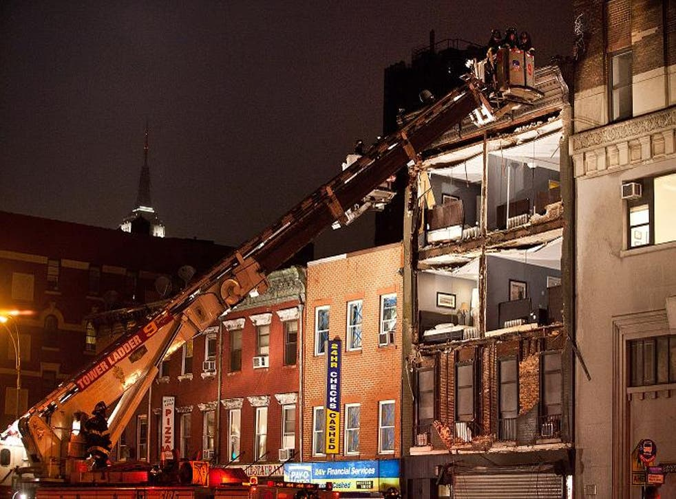 Firefighters evaluate the scene as Sandy destroys the front of a building in New York