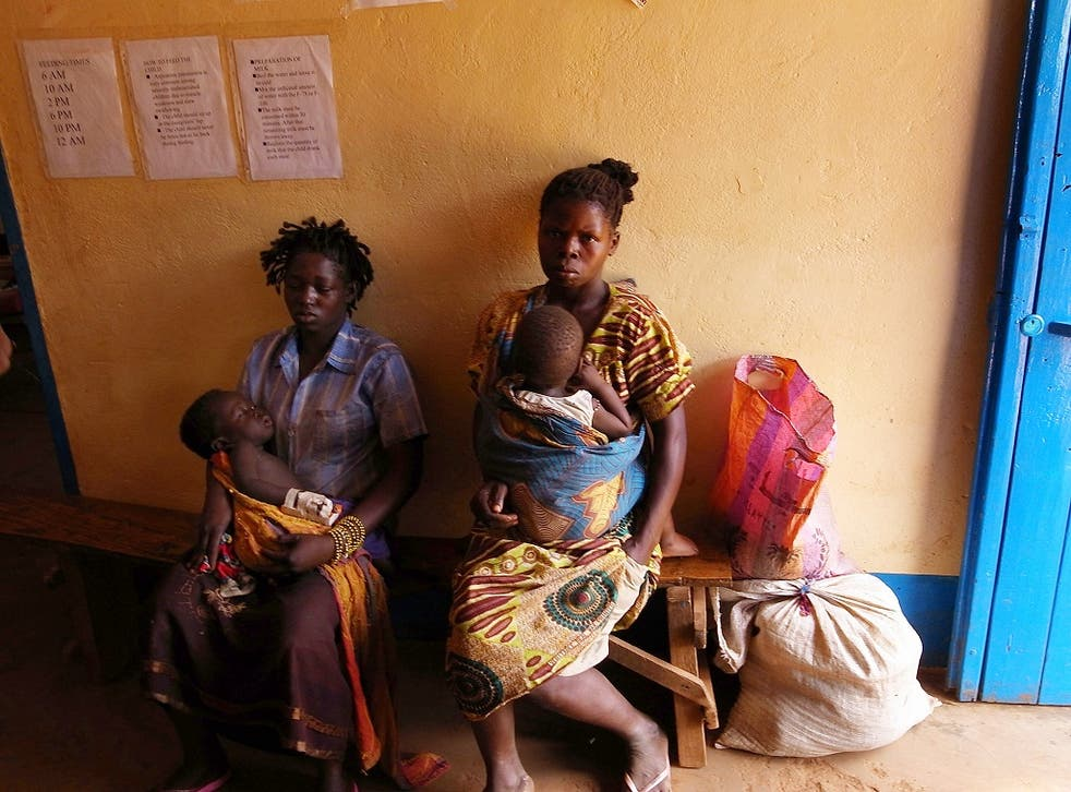 Congolese women and their children with malaria wait to see a doctor