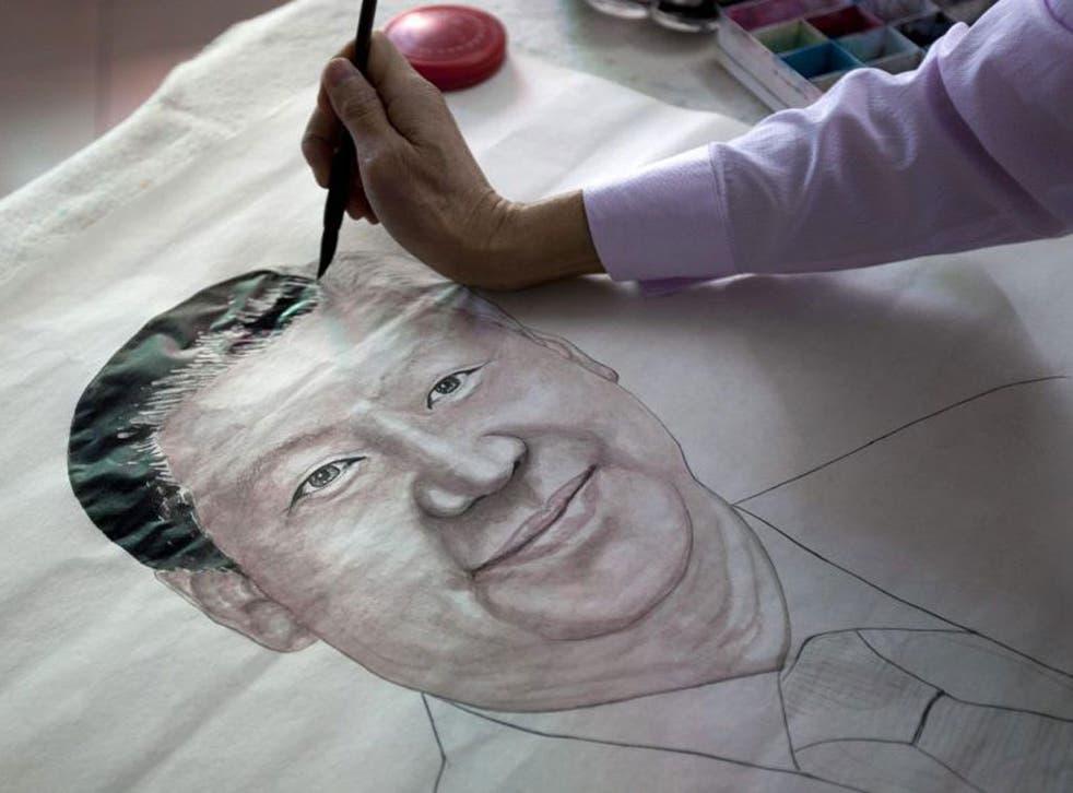 Artist Luo Jianhui draws a portrait of China's President-elect, Xi Jinping, in his studio in Guangzhou