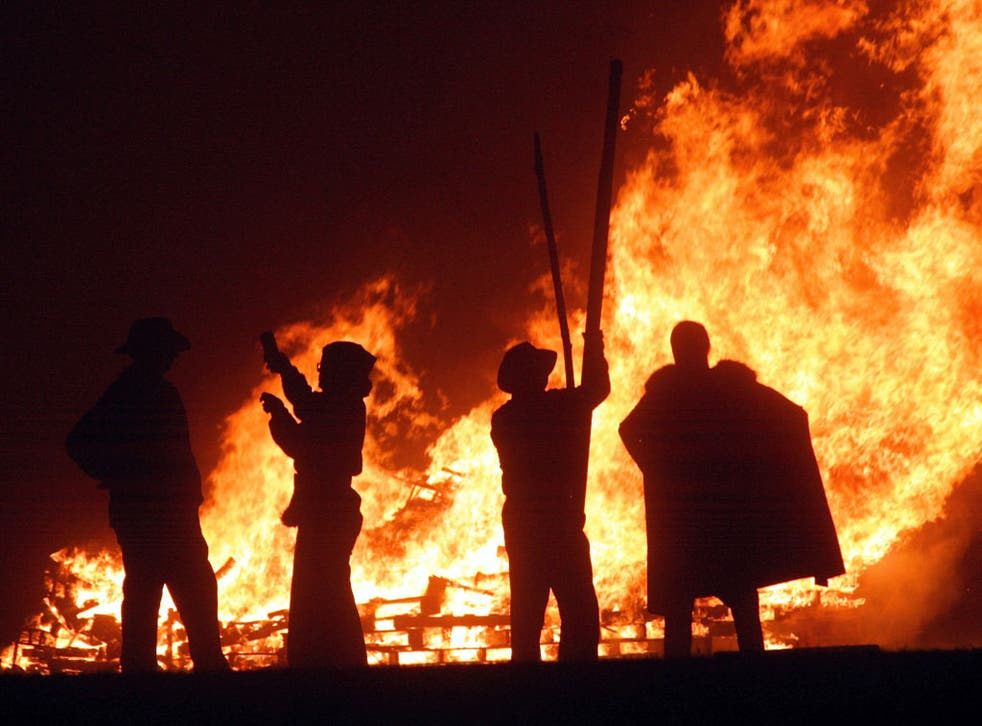 Revellers stand near the fires during the first of the Bonfire Night celebrations on September 25, 2004 in Burgess Hill, England.