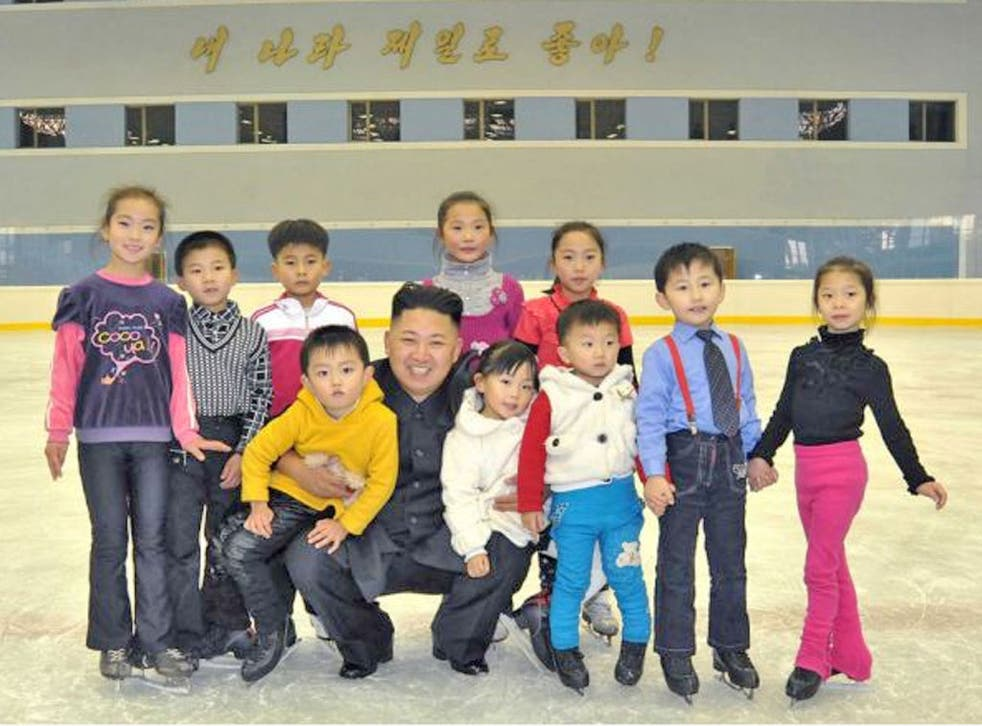 North Korean leader Kim Jong Un posing with children as he visits the open air ice skating rink in Pyongyang