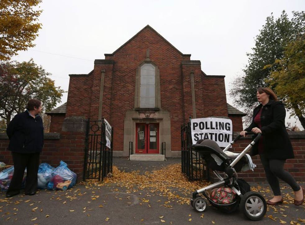 A woman pushes a pushchair past Davenport Methodist Church Polling Station in Stockport as voters go to the polls today to choose England and Wales's first police and crime commissioners