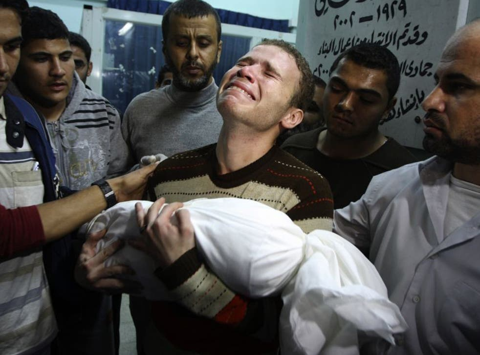 Jihad Misharawi weeps as he holds the body of his 11-month-old son Omar following an Israeli air strike in Gaza City