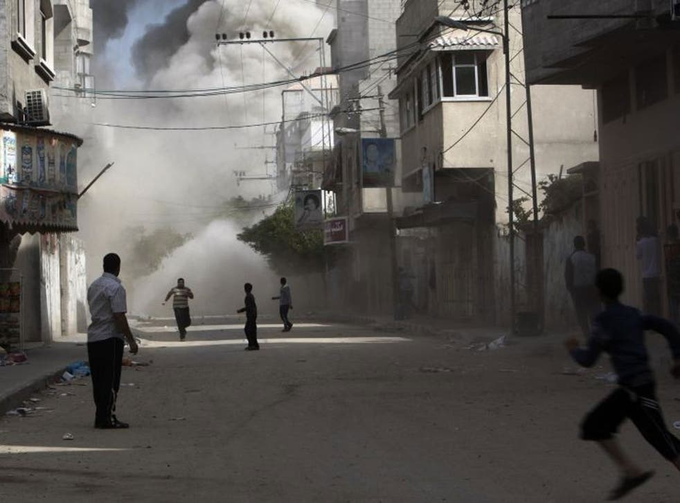 Palestinians run to take cover during an Israeli air strike on building in Gaza City