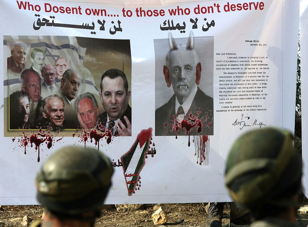Israeli soldiers stand in front of a banner with a copy of a letter from the British Foreign Secretary Arthur James Balfour to Baron Rothschild (a leader of the British Jewish community) known as the Balfour Declaration of 1917, as Palestinians, Israeli and foreign protesters demonstrate in the Israeli-occupied West Bank on November 06, 2010.