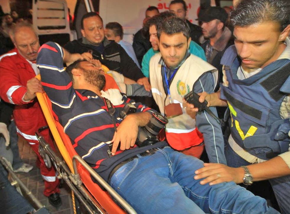 Medical staff treat a wounded Palestinian journalist in Gaza City yesterday