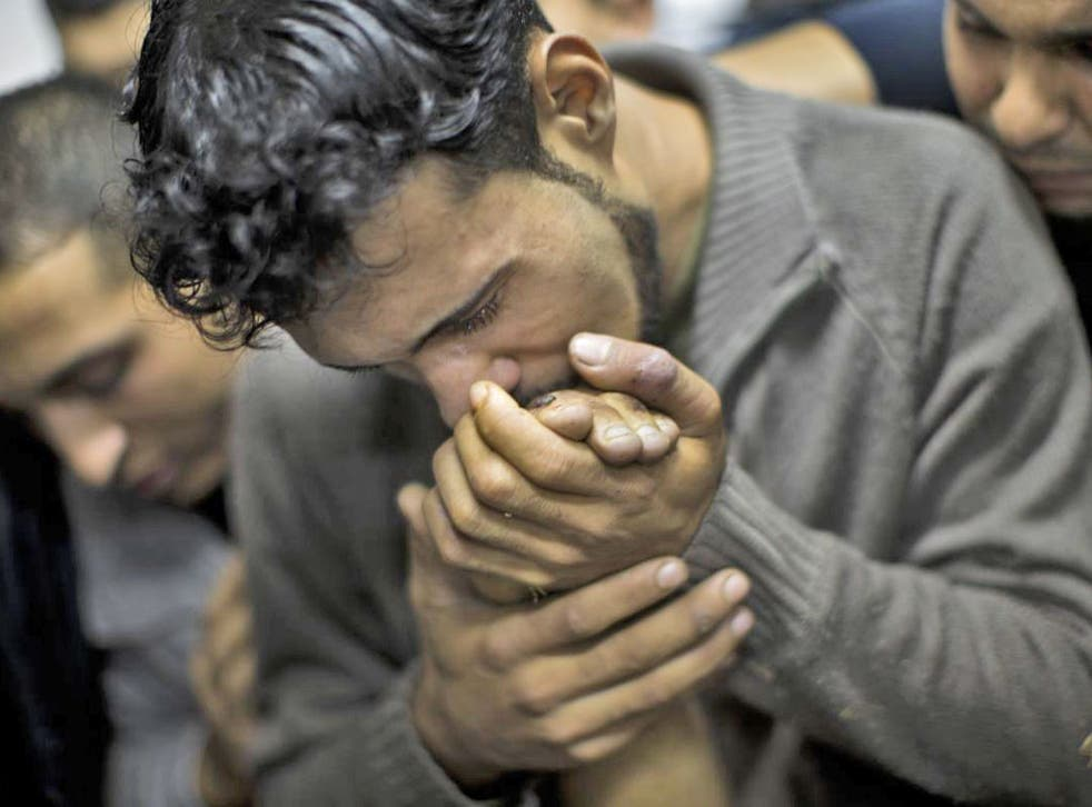 A Palestinian man kisses the hand of a dead relative in the morgue of Shifa Hospital in Gaza City
