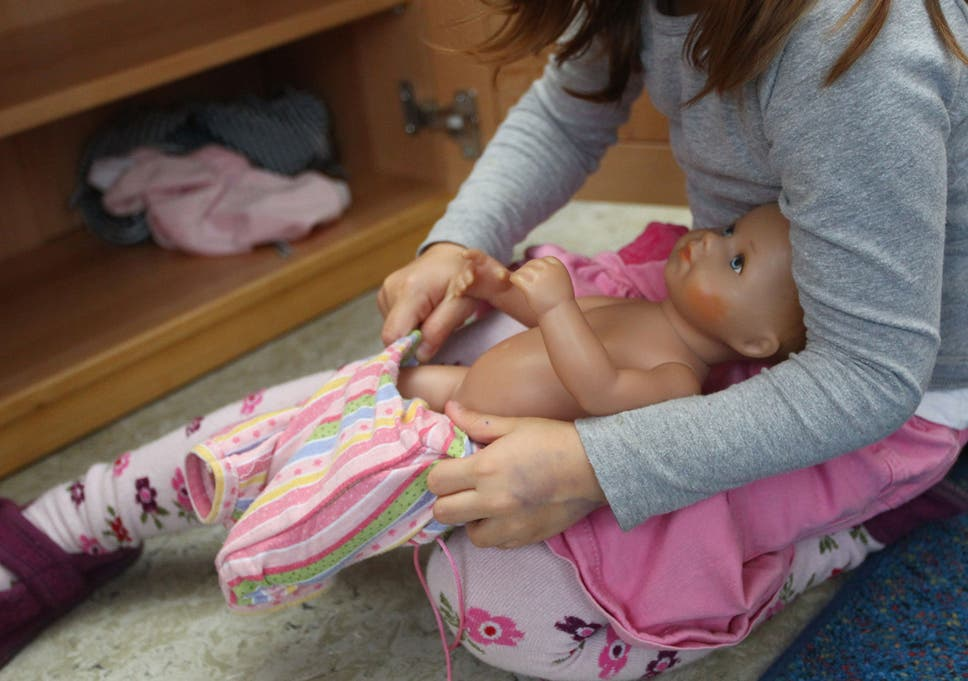 A girl gets a baby doll dressed up at a day care center for children aged