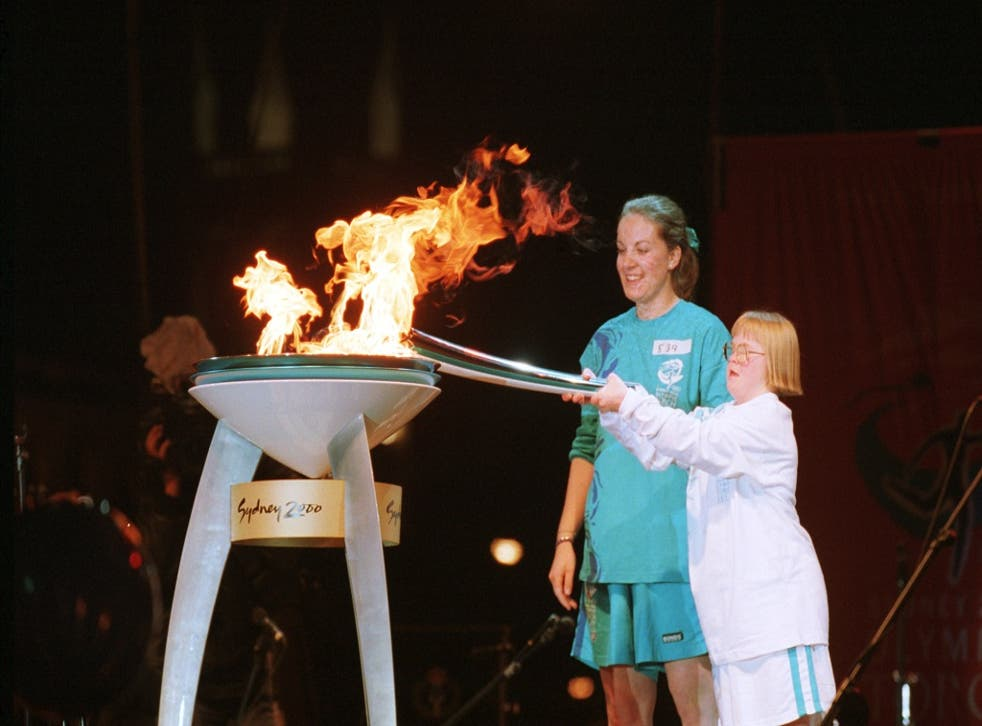 Therese Garton, who has Down's Syndrome and was a Special Olympian, lights the Olympic cauldron in Victoria Square, Adelaide, Australia. With her is her mother, Bev.