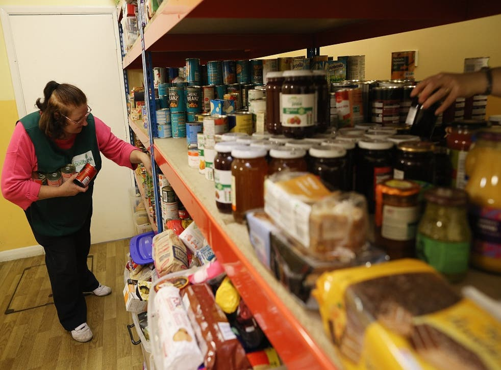 A volunteer puts together a parcel of food at a Food Bank depot at St. Paul's Church in Brixton