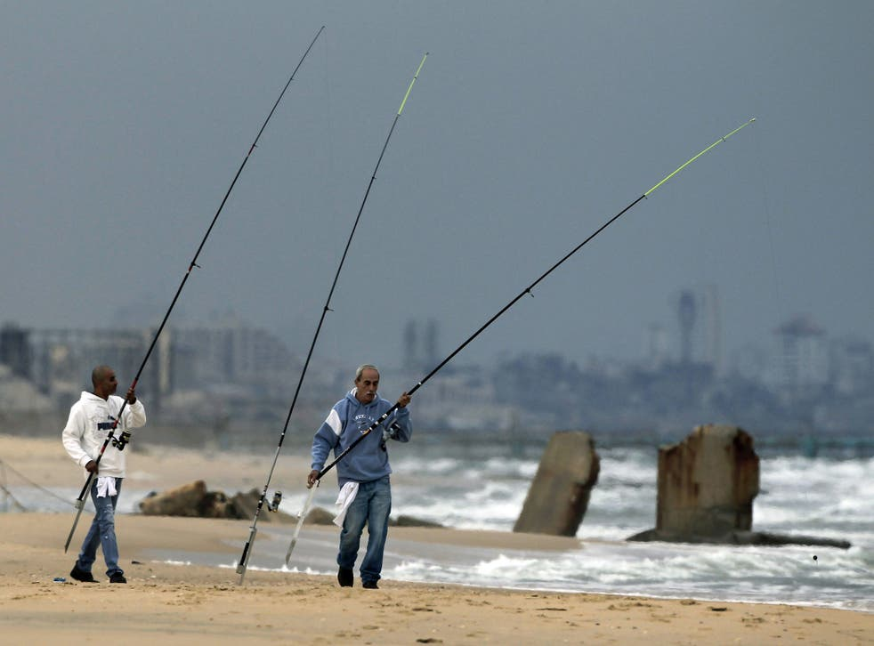Clear skies: Israelis fish on abeach near theIsrael-Gaza Strip border yesterday, as the truce holds