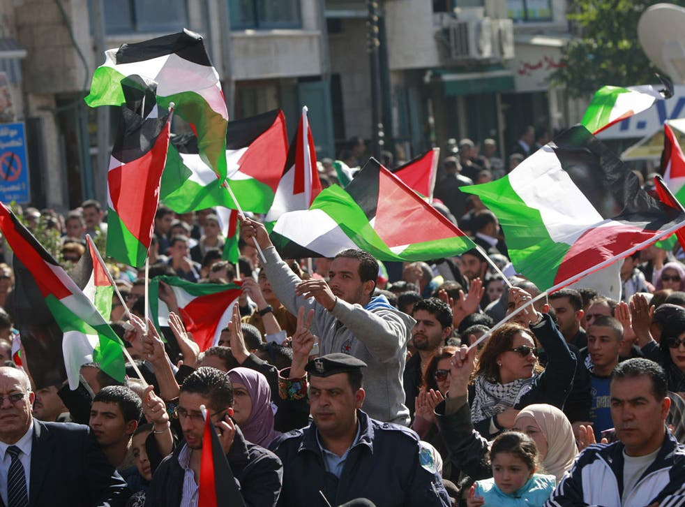 Crowds wave Palestinian flags in the West Bank city of Ramallah yesterday