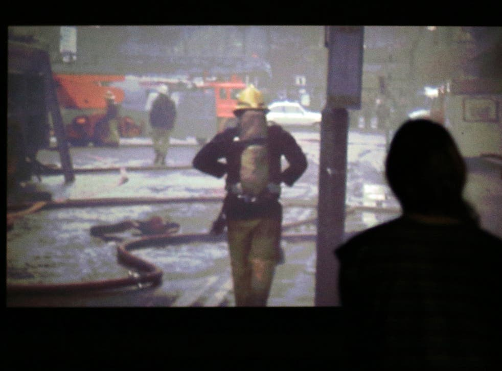 A visitor looking at Elizabeth Price's video installation 'The Woolworths Choir Of 1979 2012'