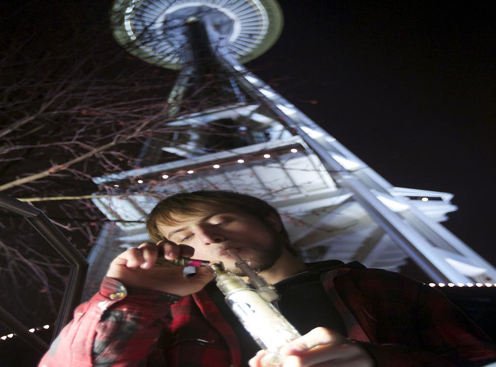 A cannabis smoker marks the start of the new law by the Space Needle in Seattle