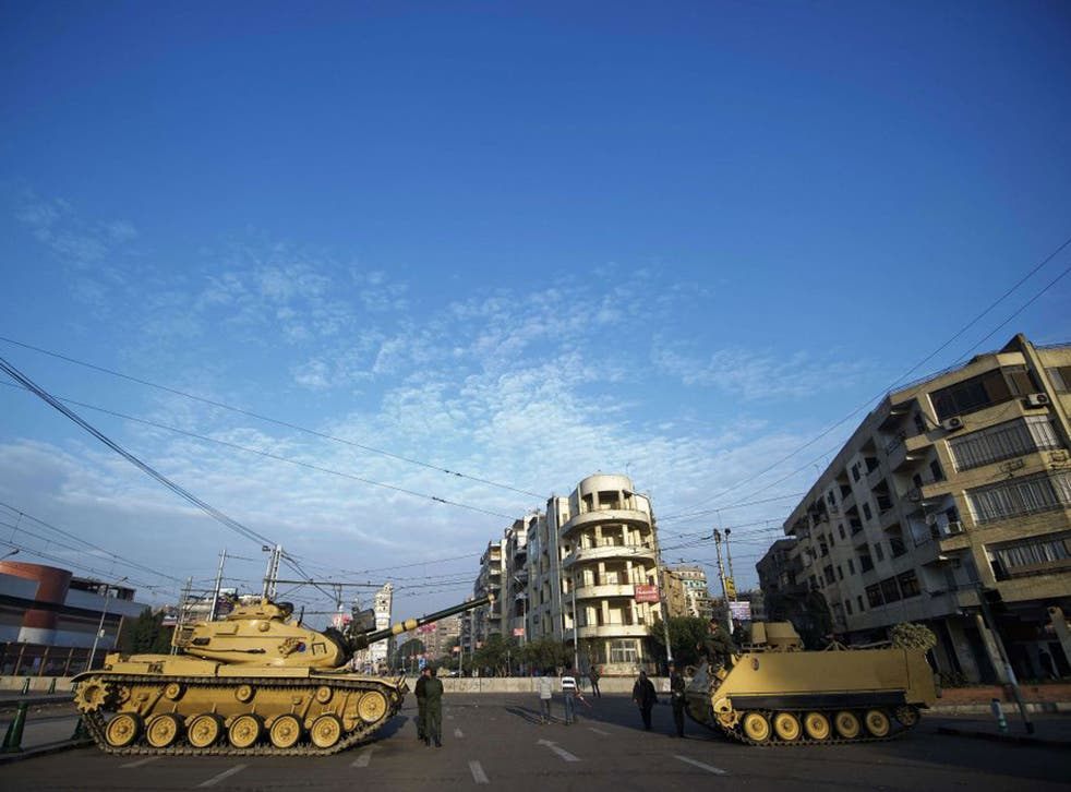 Egyptian army tanks deploy outside the presidential palace in Cairo on 8 December