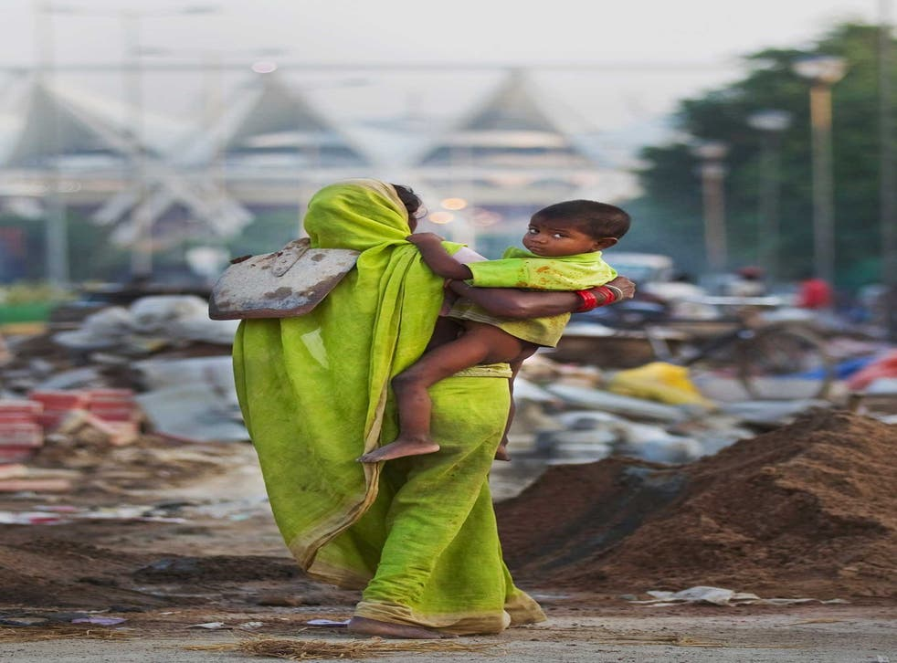 Street life: a labourer with infant and shovel in New Delhi