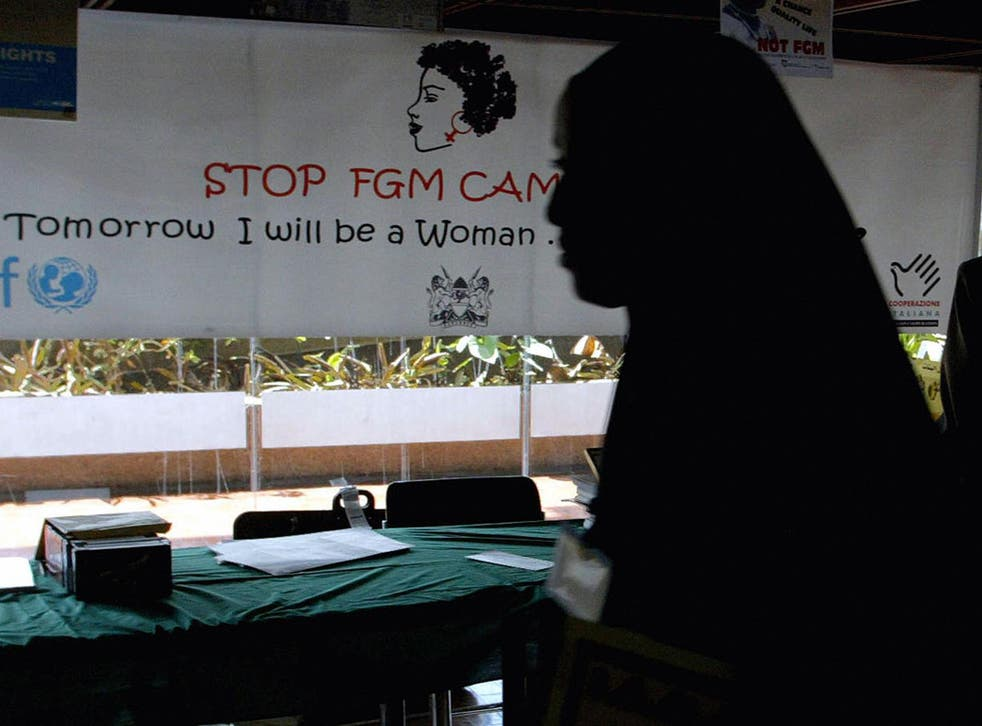 A young woman walks past a campaign banner against female genital mutilation [FGM] at the venue of an International conference, 16 September 2004 in Nairobi.