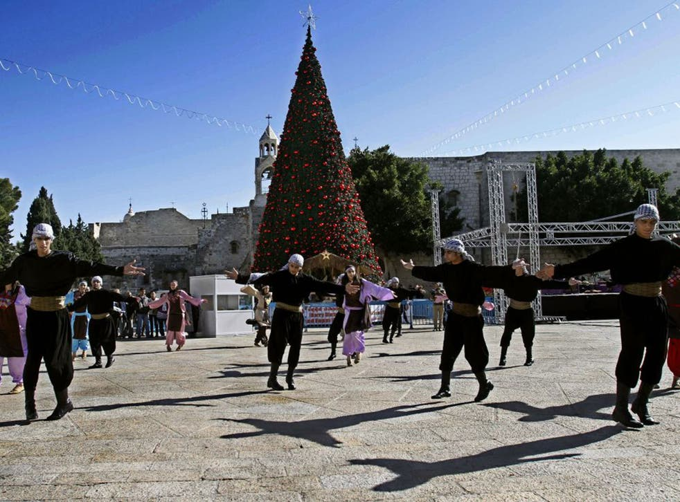 Palestinian dancers perform outside the Church of Nativity