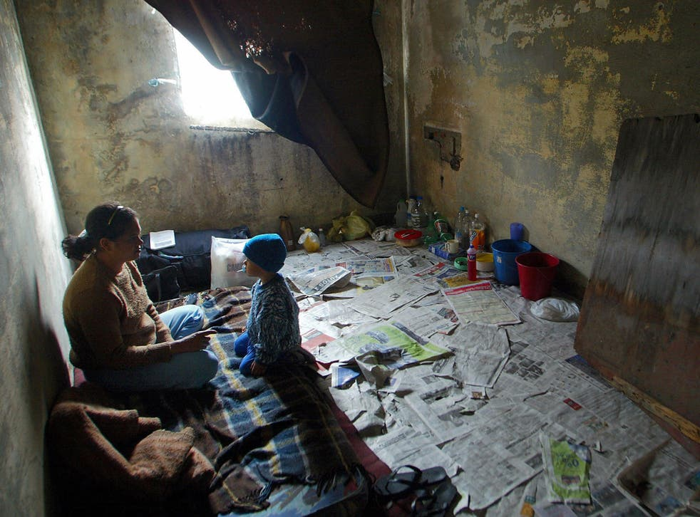A mother talks to her son in their 'bedroom' in a vacant building of Rua Maua (Maua Street), in Sao Paulo, Brazil, 29 July 2003.