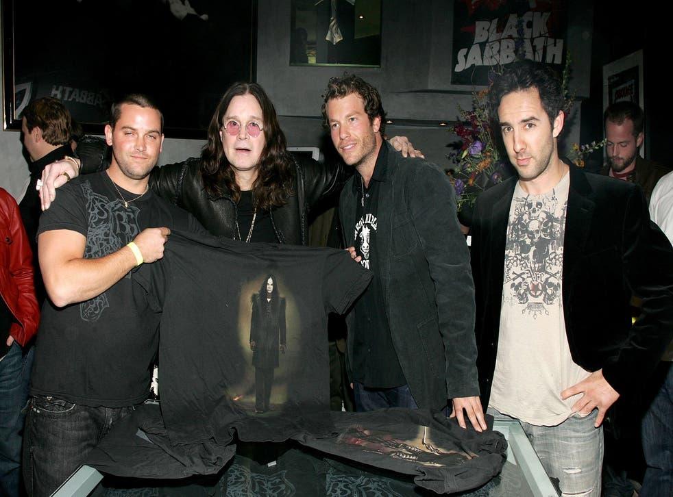 Black Sabbath holding up a T-shirt